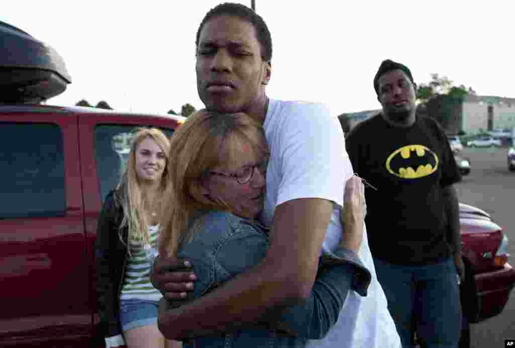 Judy Goos, deuxième à partir de la gauche, étreint l'ami de sa fille devant un lycée où des témoins de l'incident sont interrogés