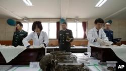 Petugas khusus untuk pemulihan dan identifikasi korban tewas Korea Selatan memasukkan sisa-sisa mayat tentara China ke dalam peti di Paju, Korea Selatan (28/3).