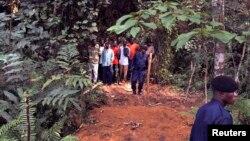 Des policiers encadrent un groupe d'hommes près des tombes nouvellement creusées sur les lieux d'un accident de train dans la jungle à Ndenga Mongo, province du Kasaï, RDC, 4 août 2007.