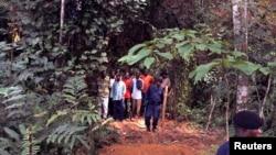 Des policiers encadrent un groupe d'homme près des tombes nouvellement creusées sur les lieux d'un accident de train dans la jungle à Ndenga Mongo, province de Kasaï, RDC, 4 août 2007.