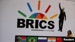ប្រតិភូម្នាក់ដើរកាត់ស្លាកសញ្ញានៃក្រុមប្រទេស BRICS នៅមុនកិច្ចប្រជុំ BRICS លើកទី១០ នៅក្នុងក្រុង Sandton ប្រទេសអាហ្វ្រិកខាងត្បូង កាលពីថ្ងៃទី២៤ ខែកក្កដា ឆ្នាំ២០១៨។