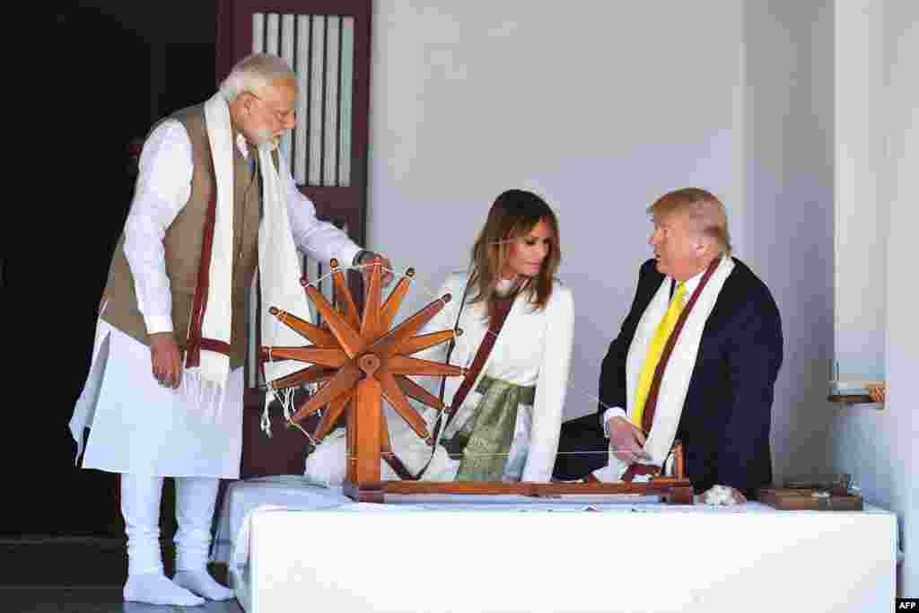 U.S. President Donald Trump and First Lady Melania Trump listen to India's Prime Minister Narendra Modi (L) as they sit next to a charkha, or spinning wheel, during their visit at Gandhi Ashram in Ahmedabad.