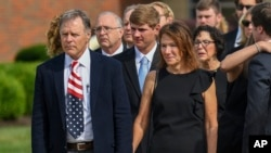 FILE - Fred and Cindy Warmbier watch as their son Otto's casket is placed in a hearse after funeral services, in Wyoming, Ohio, June 22, 2017.