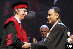 "FILE - Partha Dasgupta (R), professor at Cambridge University in Britain, is awarded ""Doctor Honoris Causa"" by the university of Louvain-la-Neuve rector Bernard Coulie, Feb. 2, 2007."
