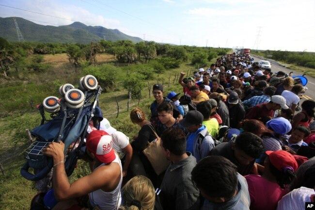 Un hombre levanta un carrito de bebé mientras cientos de migrantes intentan acomodarse en la parte trasera de un camión, entre Niltepec y Juchitan, en el estado de Oaxaca, México, el 30 de octubre de 2018.