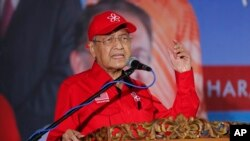 FILE - Malaysian Prime Minister Mahathir Mohamad delivers his speech during a rally for Anwar Ibrahim in Port Dickson, Malaysia, Oct. 8, 2018.