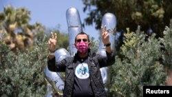 Bintang rock legendaris Ringo Starr mengenakan masker saat foto di depan patung untuk merayakan ulang tahunnya yang ke-80 di tengah pandemi Covid-19 di Beverly Hills, California, 7 Juli 2020.