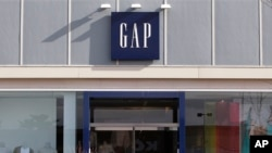 People walk past a Gap store at the Derby Street Shoppes complex in Hingham, Massachusetts, February 21, 2012