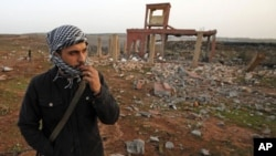 A rebel walks inside a destroyed weapons dump near Benghazi, March 5, 2011