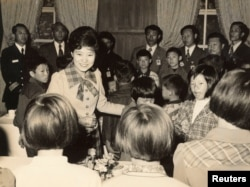 FILE - Park Geun-hye greets children when she served as her father and then-President Park Chung-hee's first lady in the 1970s, after her mother Yuk Young-soo was assassinated by a North Korean-backed gunman.