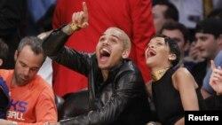 Chris Brown ríe durante el juego de baloncesto de la NBA, donde apareció de nuevo con su pareja, Rihanna.