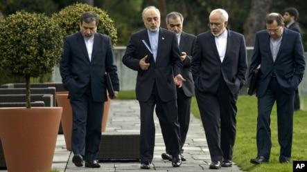 Head of Iranian Atomic Energy Organization, Ali Akbar Salehi, second from left, and Iranian Foreign Minister Javad Zarif, second from right, walk together during negotiations at an hotel in Lausanne, Switzerland, March 29, 2015.