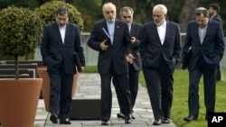 Head of the Iranian Atomic Energy Organization, Ali Akbar Salehi, second from left, and Iranian Foreign Minister Javad Zarif, second from right, walk together during negotiations at a hotel in Lausanne, Switzerland, March 29, 2015.