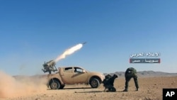 FILE - May 25, 2017 photo provided by the government-controlled Syrian Central Military Media, shows Syrian government troops firing multiple launcher rockets at insurgent group's position, in the Syrian province of Homs.