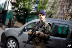FILE - A French soldier stands near the scene where soldiers were hit and injured by a vehicle in the western Paris suburb of Levallois-Perret near Paris, France, Aug. 9, 2017.