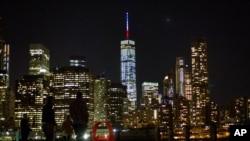 Ngọn tháp trên đỉnh tòa nhà Trung tâm Thương mại Thế giới được thắp sáng với các màu xanh, trắng và đỏ, 13/11/2015.