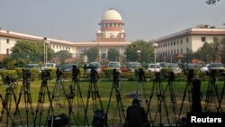 A television journalist sets his camera inside the premises of the Supreme Court in New Delhi, Feb. 18, 2014.