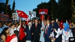 Presiden Turki, Recep Tayyip Erdogan, tengah, ditemani oleh istrinya Emine, kiri, berbaris bersama kelaurga para korban upaya kudeta yang gagal 15 Juli 2016 (foto: Presidency Press Service via AP, Pool)
