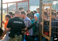 A Macedonian border policeman opens a gate for the refugees and migrants to reach the southern Macedonian town of Gevgelija, Sept. 11, 2015. Hundred of thousands migrants and refugees trying to reach the heart of Europe via Turkey, Greece, the Balkans and