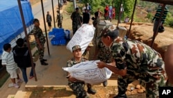Nepalese soldiers load U.S. AID relief sacks at a staging area near Saturday's massive earthquake's epicenter in the town of Gorkha, Nepal, April 28, 2015.