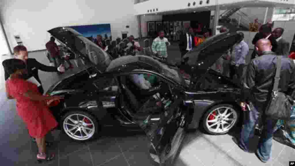 Wani dan jarida a Najeriya na duba wata sabuwar mota kirar Porsche Cayman S a cikin wani gidan tallar motoci a tsuburin Victoriya dake jihar Ikko a Najeriya. Alhamis, Mayu 9, 2013.