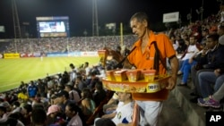 A vendor sells tequenos (cheese sticks) during the baseball game between the Leones de Caracas and the Navegantes del Magallanes in Caracas, Venezuela, Oct. 27, 2015.