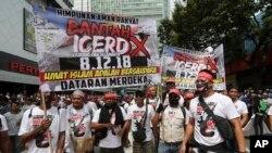 Para pengunjuk rasa memegang spanduk dalam reli merayakan langkah pemerintah membatalkan rencana untuk meratifikasi konvensi anti-diskriminasi U.N. yang disebut ICERD, di Kuala Lumpur, Malaysia, Sabtu, 8 Desember 2018.