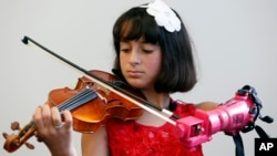 Isabella Nicola Cabrera, 10, plays her violin with her new prosthetic at the engineering department of George Mason University in Fairfax, Virginia, April 20, 2017.