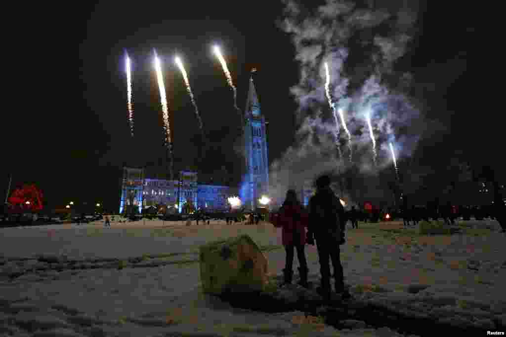 Children watch fireworks during a Christmas light illumination ceremony on Parliament Hill in Ottawa, Canada, Dec. 5, 2013.