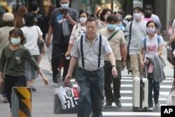 Para pejalan kaki menyeberang jalan di distrik perbelanjaan di Taipei, Taiwan, di tengah pandemi Covid-19, Kamis, 29 Oktober 2020.