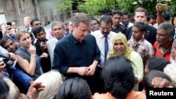 Britain's Prime Minister David Cameron talks with Tamil people at the Sabapathi Pillay Welfare Centre in Jaffna, about 400 km (250 miles) north of Colombo, Nov. 15, 2013.