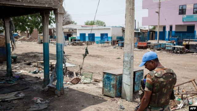 A United Nations peacekeeper looks at the destruction in downtown Malakal, South Sudan, on March 4, 2014.