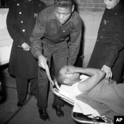 Thomas Hagan, 22, is carried in police custody from Jewish Memorial Hospital en route to Bellevue Hospital in New York, Feb. 21, 1965.
