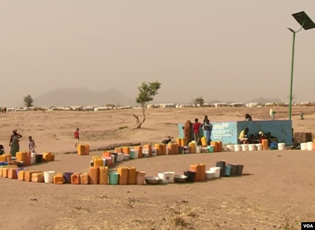 FILE - Refugees set out containers waiting for UNHCR to fill them with water, at Minawao refugee camp, northern Cameroon, Feb. 9 2018. (M. Kindzeka/VOA)