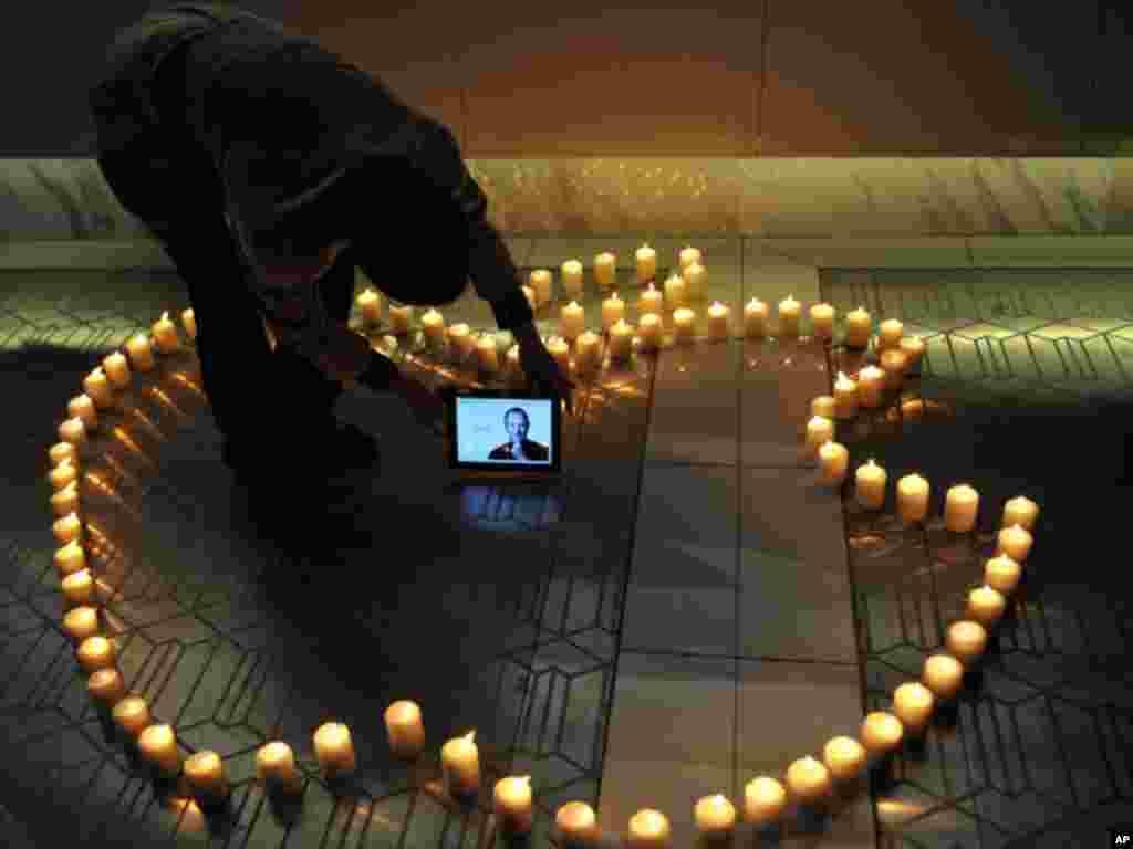 在中国西南部的四川省,一位男子把有乔布斯照片的iPad放在组成苹果公司标记图形的蜡烛中间,纪念这位苹果公司共同创始人。(10月6日)