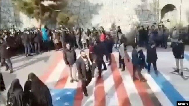 Algunas personas caminan sobre las banderas de Estados Unidos e Israel en la Universidad Shahid Beheshti de Teheran el 12 de enero de 2020, mientras que otras dan la vuelta alrededor, en esta foto de Reuters tomada de un video en las redes sociales.