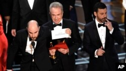 "Jordan Horowitz shows the envelope revealing ""Moonlight"" as the true winner of best picture at the Oscars, Feb. 26, 2017, at the Dolby Theatre in Los Angeles. . Host Jimmy Kimmel and presenter Warren Beatty look on from right."