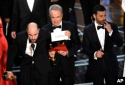 "FILE - Jordan Horowitz shows the envelope revealing ""Moonlight"" as the true winner of best picture at the Oscars, Feb. 26, 2017, at the Dolby Theatre in Los Angeles."