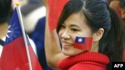 一名台灣女子臉頰上貼著台灣旗幟並手舉台灣旗幟參加集會。(資料圖片)