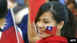 资料照:一名台湾女子脸颊上贴着台湾旗帜并手举台湾旗帜参加集会。