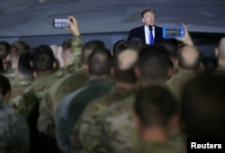 FILE - President Donald Trump speaks to members of the U.S. military after his summit meeting with North Korea's Kim Jong Un in Vietnam, during a refueling stop at Elmendorf Air Force Base in Anchorage, Alaska, Feb. 28, 2019.