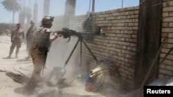 A member of the Iraqi security forces opens fire during clashes with fighters from Sunni militant group Islamic State of Iraq and the Levant (ISIL) in Ibrahim bin Ali village, west of Baghdad, June 24, 2014. Iraqi army soldiers clashed with militants from