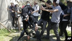 People try to help a riot policeman after he was hit by demonstrators during a protest marking the 1973 military coup in Santiago September 11, 2011.