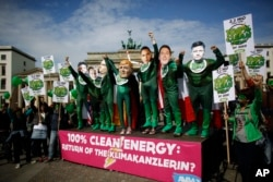 Climate activists in green costumes and with masks of the G7 leaders attend a protest in front of the Brandenburg Gate near a building hosting the 'Petersberg Climate Dialogue' conference in Berlin, Germany.