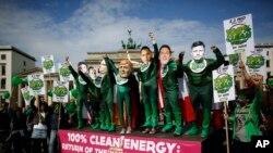 Des activistes de l'environnement en costumes verts portant des masques des dirigeants du G7 assistent à une manifestation devant la Porte de Brandebourg à Berlin, en Allemagne, le 15 mai 2015. (AP Photo/Markus Schreiber)