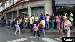İnsanlar Karakasda mağaza qarşısında növbədə