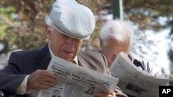 Penzioneri čitaju novine u parku u Beogradu (Foto: AP/Darko Vojinović)