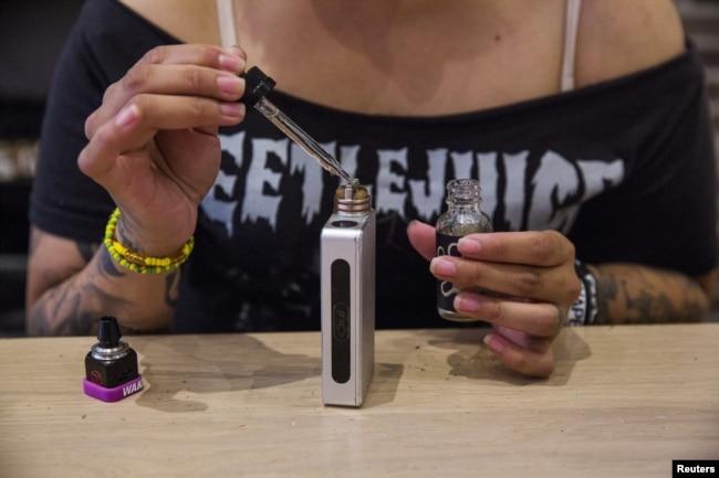 Seorang perempuan menambahkan penguat rasa ke dalam alat rokok elektrik sembari menunggu pelanggan di toko rokok elektrik, Henley Vaporium, di New York, 23 Juni 2015.