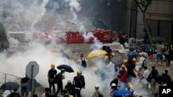 홍콩 입법부 밖에서 경찰들이 '범죄인인도조례' 개정안에 반대하는 시위대를 향해 최루탄을 발사하고 있다.