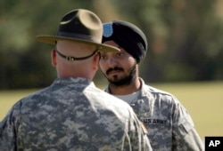 FILE - U.S. Army Spc. Simran Lamba, right, speaks to his drill sergeant following his graduation from basic combat training at Fort Jackson, S.C., Nov. 10, 2010. Lamba was the first enlisted soldier to be granted a religious accommodation for his Sikh articles of faith since 1984.